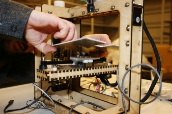 A pair of hands replacing the build platform on a 3D printer